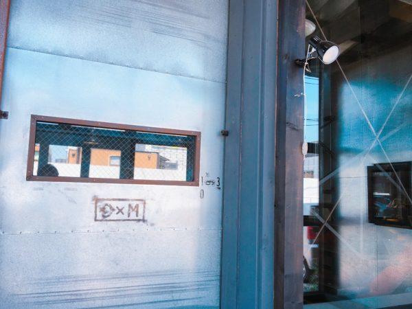 D×Mと書かれた重厚感のあるドアを開けると、コーヒー豆と大きな焙煎機が目に入る。